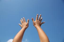 両手を空にかざすイメージ